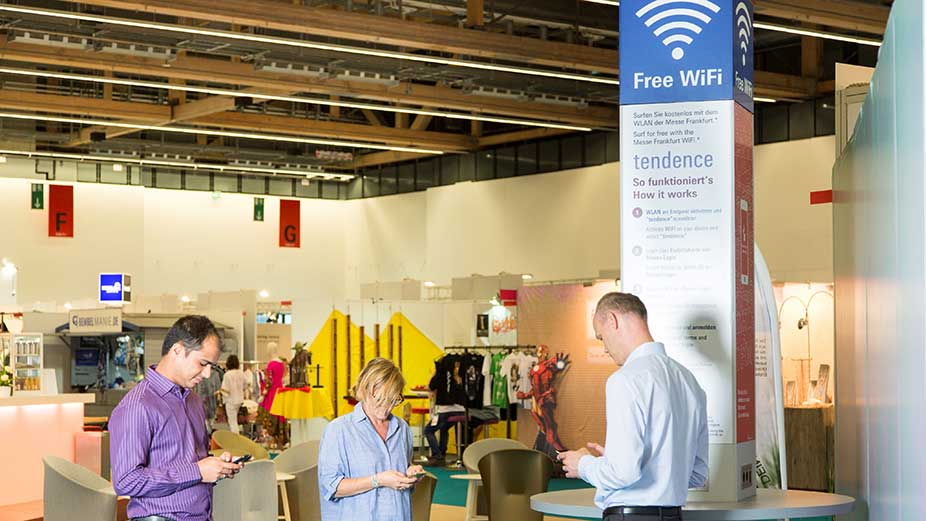 Three trade fair visitors use the free Wi-Fi access at the Frankfurt Trade Fair