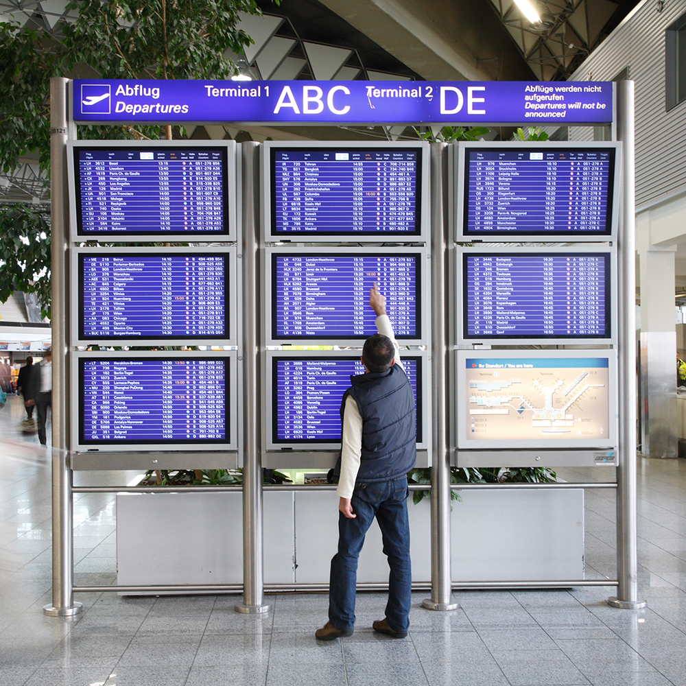 A man stands in an airport in front of a departure table